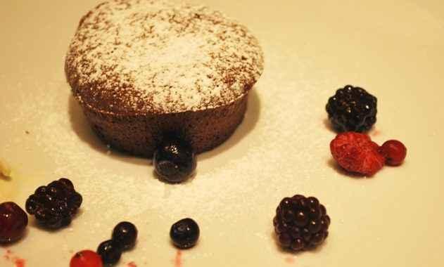 Flan al cioccolato guarniti con gelato e frutti di bosco